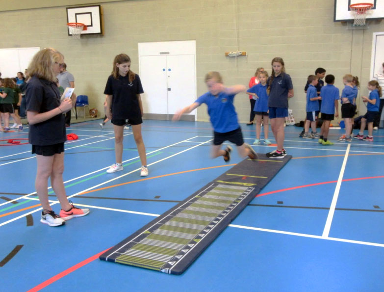 Year 8 Young Leaders record the long jump scores in a close competition.